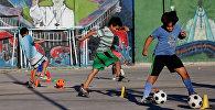 Дети играют в футбол перед фреской Папы Фрэнсиса в трущобах 1-11-14 в Буэнос-Айресе, Аргентина