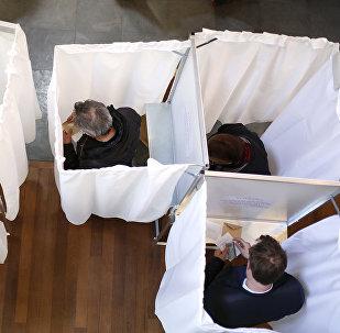 Избиратели выбирают своих кандидатов в кабинах для голосования на избирательном участке в Париже 23 апреля 2017 года во время первого тура президентских выборов во Франции