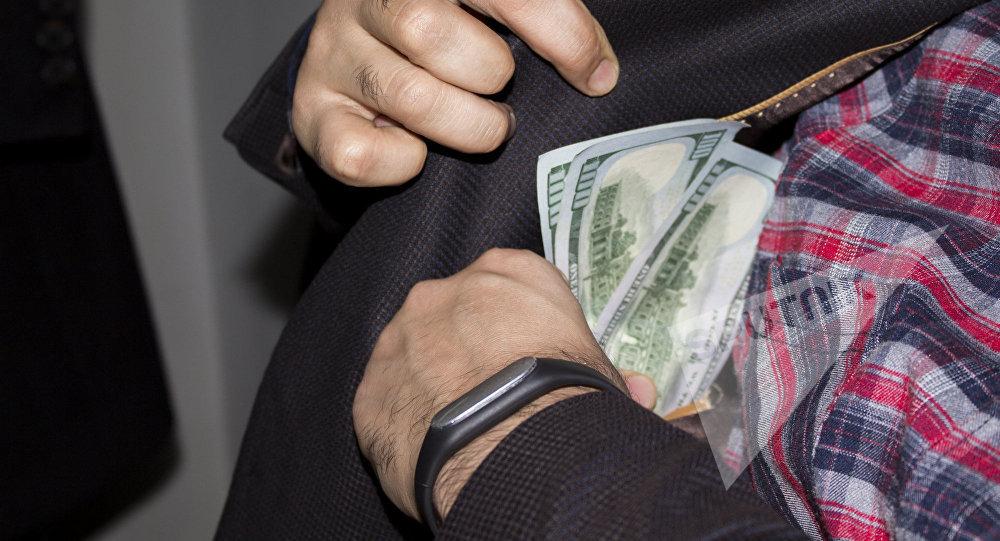 Мужчина прячет деньги во внутренний карман, фото из архива