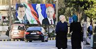 Сирийцы, идущие мимо гигантского плаката с президентом Сирии Башаром Асадом и президентом России  Владимиром Путиным, фото из архива