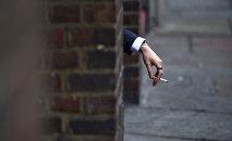 Мужчина держит в руке сигарету, фото из архива