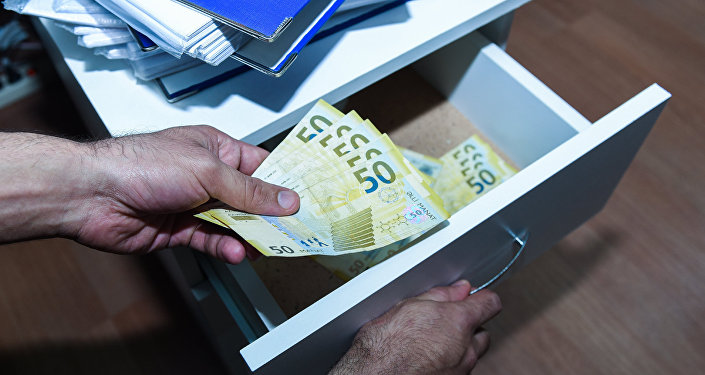 Мужчина прячет деньги  в ящик комода, фото из архива