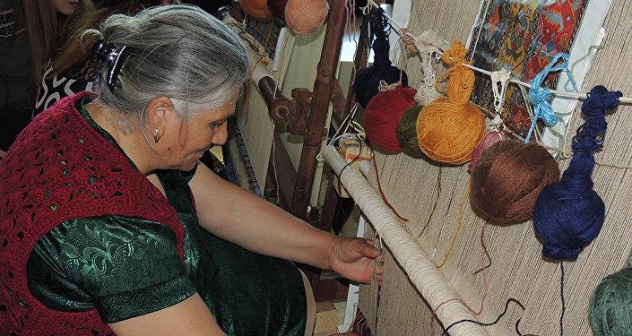 Женщина, ткущая ковер, архивное фото