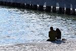 Молодая пара сидит на берегу моря в Баку, фото из архива