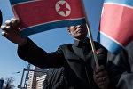 Жители города с флагами КНДР во время торжественной церемонии открытия нового жилого комплекса на улице Рёмён в Пхеньяне