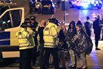 Сотрудники служб экстренной помощи опрашивают людей близ Манчестер Арены после сообщения о взрыве на месте во время концерта певицы Арианы Гранде в Манчестере, Англия, в понедельник, 22 мая 2017 года