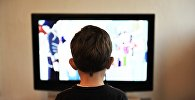 Ребенок за просмотром телевизора, фото из архива