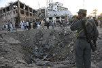 Люди рядом с кратером, созданным массовым взрывом перед посольством Германии в Кабуле, Афганистан, в среду, 31 мая 2017 года