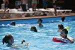 Люди купаются в бассейне, фото из архива