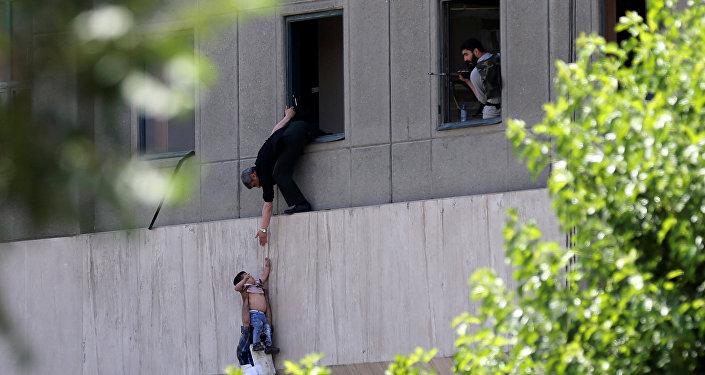 Человек передает ребенка охраннику из окна парламента Ирана в Тегеране