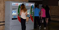 Девушка производит платеж через терминал оплаты на станции бакинского метрополитена