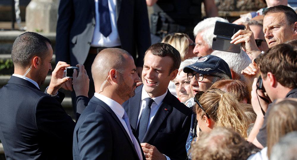 Полицейский в штатском фотографирует президента Франции Эммануэля Макрона со сторонниками его политики, фото из архива