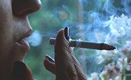 Женщина курит сигарету, фото из архива