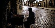 Мужчины играют в нарды на одной из улиц старого города в Баку