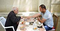 Шакир Алиев играет в шашки с сотрудником Sputnik Азербайджан Ильхамом Мустафа