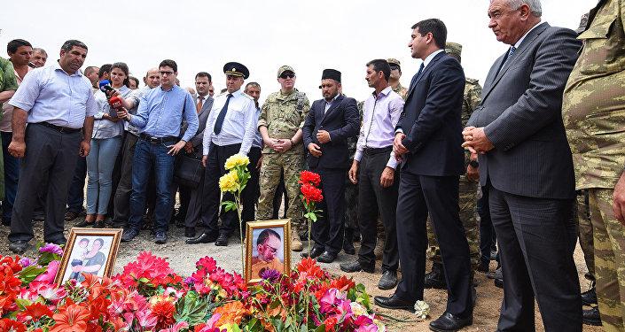 Военные атташе зарубежных государств и официальные лица Азербайджана у могил убитых в селе Алханлы Сахибы Гулиевой и ее двухлетней внучки Захры