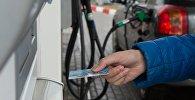 Мужчина расплачивается кредитной картой на автозаправочной станции