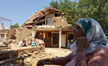 Женщина сидит во дворе своего дома, разрушенного землетрясением в деревне Ялычифтлик недалеко от курортного города Бодрум в провинции Мугла, Турция, 21 июля 2017 года