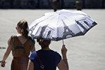 Женщина с зонтиком в жаркий летний день, фото из архива