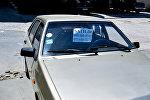 Листок со словом Продается под лобовым стеклом автомобиля, фото из архива