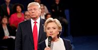 Республиканский кандидат в президенты США Дональд Трамп слушает, как кандидат от Демократической партии Хиллари Клинтон отвечает на вопрос от аудитории во время дебатов в президентской мэрии в Вашингтонском университете в Сент-Луисе, штат Миссури, США, 9 октября 2016 года