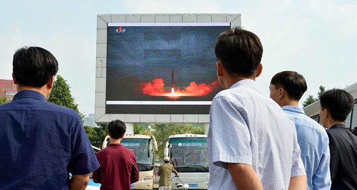 Жители северокорейской столицы следят за новостями о запуске ракеты средней дальности Hwasong-12 на электронном табло в Пхеньяне, Северная Корея, 30 августа 2017 года