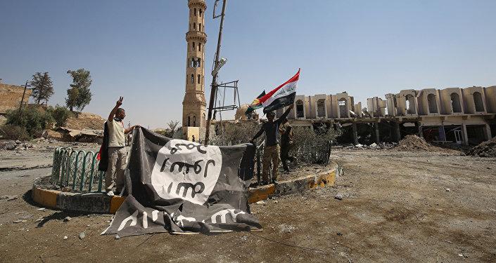 Боевики коалиции Силы народной мобилизации, сражающейся на стороне иракского правительства, фотографируются с флагом ИГ в городе Талль-Афаре, Ирак, 27 августа 2017 года