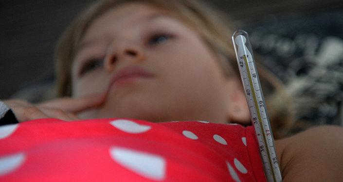Девочка с симптомами гриппа измеряет температуру, фото из архива