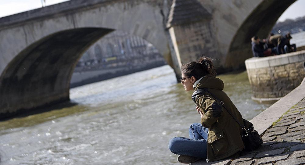 Женщина сидит на берегу реки Сена в Париже, фото из архива