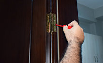 Мужчина демонтирует дверь, фото из архива