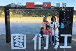 Туристы фотографируются на фоне постера на границе между Северной Кореей и Китаем, 30 августа 2017 года