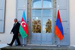 Охранник проходит мимо азербайджанского (слева) и армянского флага на открытии переговоров в Женеве, Швейцария, 16 октября 2017 года