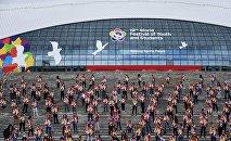 Участники XIX Всемирного фестиваля молодежи и студентов во время танцевального флешмоба у ледового дворца Большой в Сочи