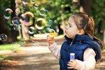 Маленькая девочка пускает мыльные пузыри