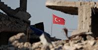 Руины на турецко-сирийской границе на фоне флага Турции, 11 октября 2017 года