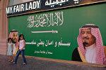 Девочки стоят рядом с плакатом, изображающим короля Саудовской Аравии Салмана бен Абдулазиза Аль Сауда и наследного принца Мохаммеда бин Салмана в Джидде, Саудовская Аравия, 10 ноября 2017 года