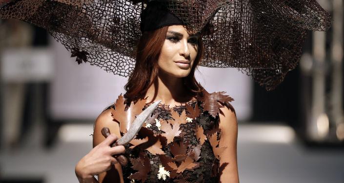 Модель в наряде из шоколада на кулинарном фестивале в Бейруте