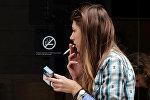 Девушка курит у входа в кофейню