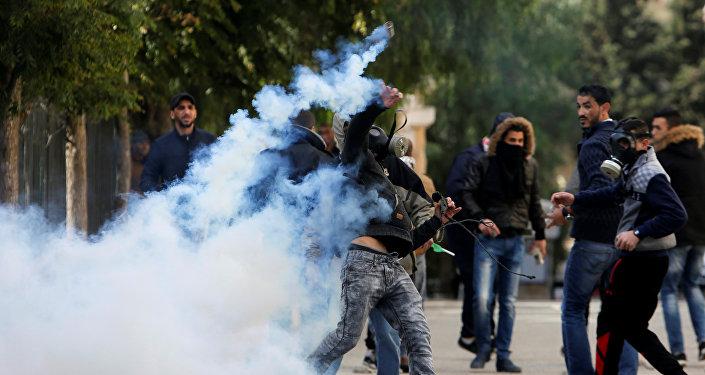 Палестинский протестующий бросает баллон со слезоточивым газом в сторону израильских военных во время столкновений в Вифлееме на Западном берегу, 7 декабря 2017 года