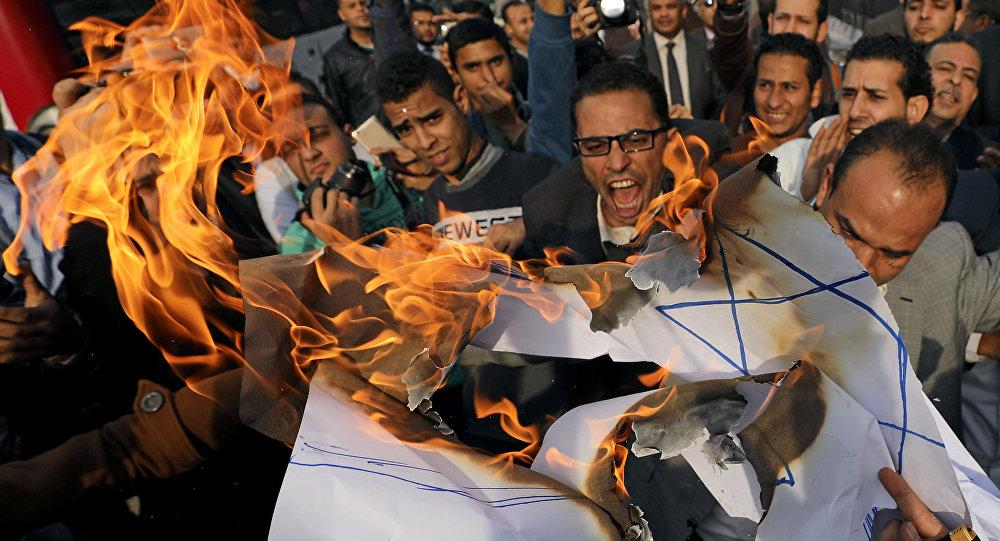 Протестующие кричат лозунги и сжигают израильский флаг во время антиизраильского протеста в Каире, Египет, 10 декабря 2017 года