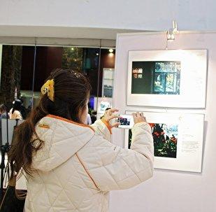 Посетительница на открытии выставки победителей конкурса имени Андрея Стенина в Пекине