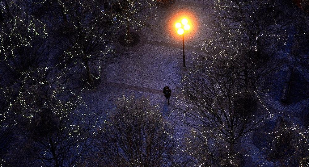 Мужчина идет по парку, украшенному к Новому году