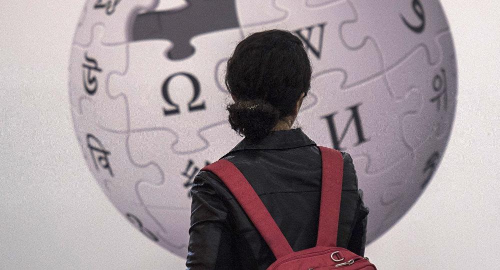 Посетительница стоит перед стендом с изображением логотипа онлайн энциклопедии Wikipedia