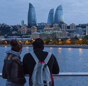 Молодая пара любуется видом на вечерний Баку