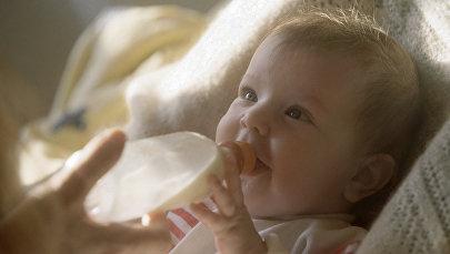 Маленькая девочка пьет из бутылочки, фото из архива