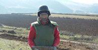 Сотрудник ANAMA со снарядом, обнаруженном на территории села Алпоут Газахского района
