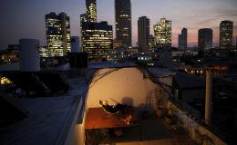 60-летний Александр Флашенберг, сидя на стуле на крыше своего дома в Тель-Авиве, наслаждается видом на море. Как говорит Александр, крыша - это его личное убежище и возможность отдохнуть от работы