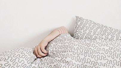 Женская рука видна из под одеяла, фото из архива