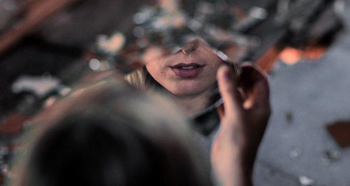 Девушка рассматривает свое отражение на куске зеркала, фото из архива