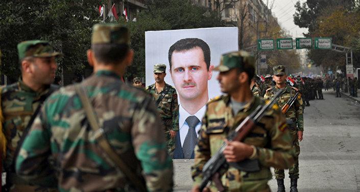 Сирийские солдаты проходят мимо портрета президента Башара аль-Асада во время правительственного праздника, посвященного первой годовщине возвращения северного сирийского города Алеппо, недалеко от площади Саадаллы аль-Джабири 21 декабря 2017 года